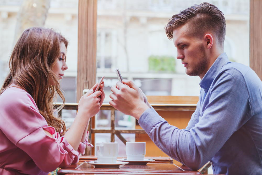 Two people using phones over coffee